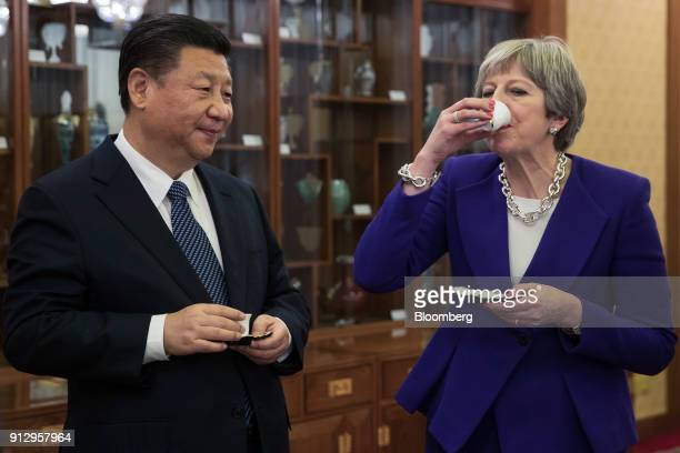 Theresa May UK prime minister right drinks from a cup as she stands next to Xi Jinping China's president during a tea ceremony at the Diaoyutai State...