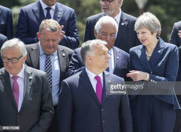 Theresa May UK prime minister right speaks with Viktor Orban Hungary's prime minister center as they stand with JeanClaude Juncker president of the...