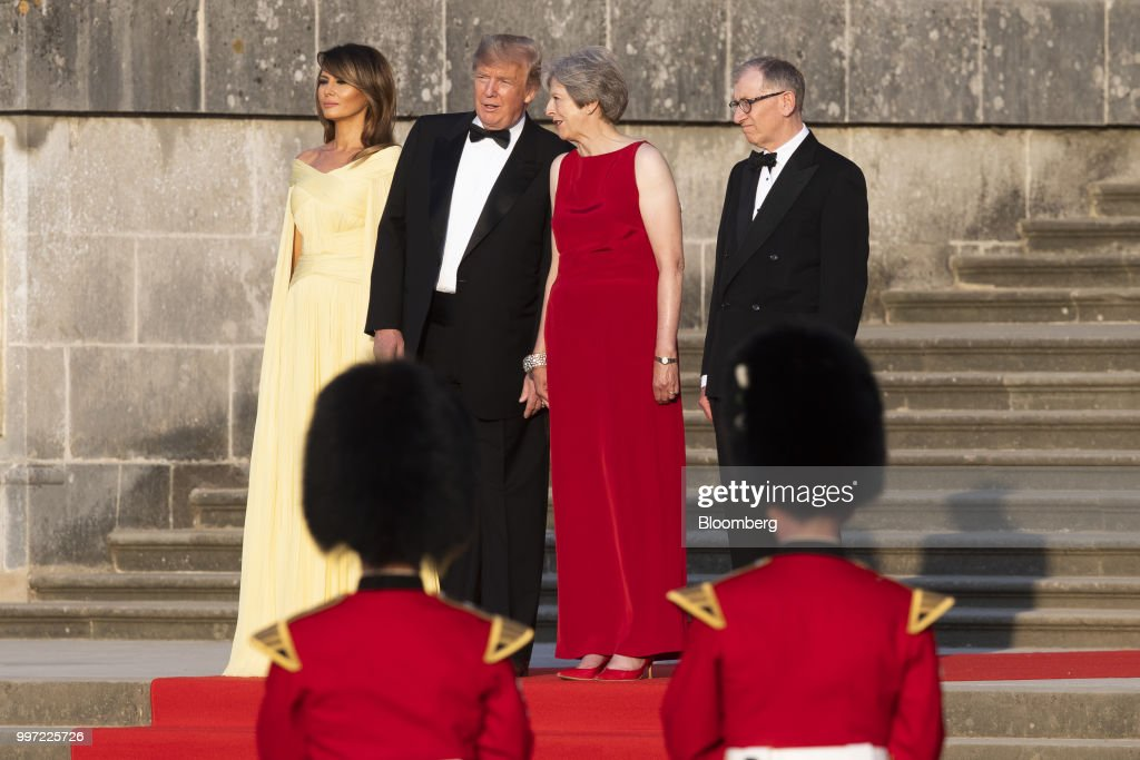 Theresa May, U.K. prime minister, second right, speaks with U.S. President Donald Trump, second left, while U.S. First Lady Melania Trump, right, and Philip May, husband of May, stand during a live military performance by the bands of the Scots, Irish and Welsh Guards ahead of a dinner at Blenheim Palace, in Oxfordshire, U.K., on Thursday, July 12, 2018. Trump and the first lady will meet British business leaders at the black-tie dinner attended by more than 100 guests. Photographer: Will Oliver/Pool via Bloomberg