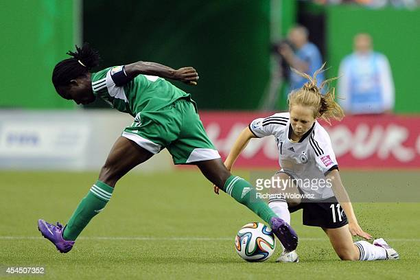 Theresa Panfil of Germany trips Ebere Okoye of Nigeria during the FIFA Women's U20 Final at Olympic Stadium on August 24 2014 in Montreal Quebec...