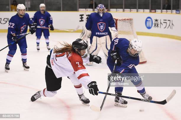 Theresa Schafzahl of Austria and Morgane Rihet of France battle for the puck during the Women's Ice Hockey Olympic Qualification Final game between...