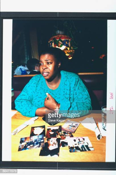 Theresa Smith sister to serial killer Jeffrey Dahmer's murder victim Eddie Smith sitting w pics of bro on table in unident restaurant