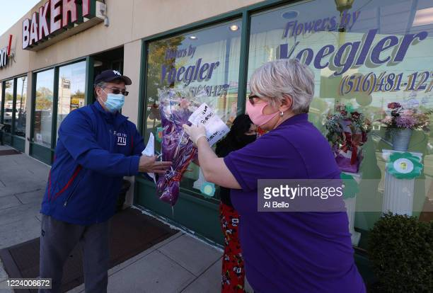 Theresa Soto delivers a prepaid flower arrangement to a customer on May 10 2020 in Merrick New York Theresa Soto is the owner of Flowers by Voegler...