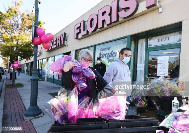 Theresa Soto places flowers outside her Florist store on May 10 2020 in Merrick New York Theresa is the owner of Flowers by Voegler She and her staff...