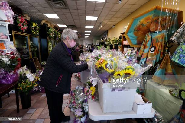 Theresa Soto prepares to deliver a floral arrangement to a customer waiting outside her store on May 10 2020 in Merrick New York Theresa Soto is the...