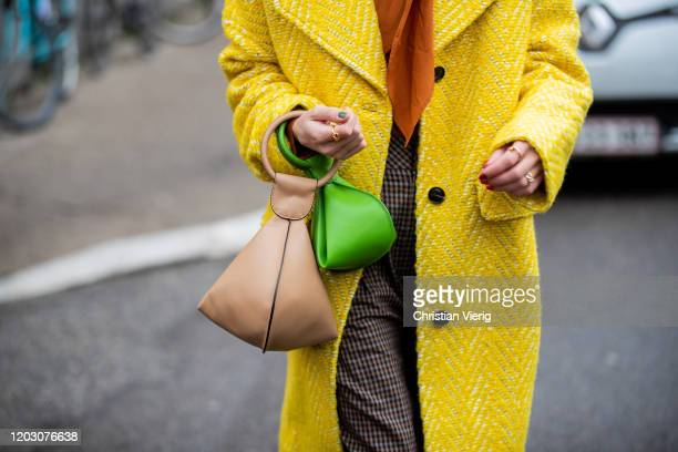 Therese Hellström seen wearing yellow coat orange blouse brown checkered pants heels with socks green brown bag outside By Malene Birger during...