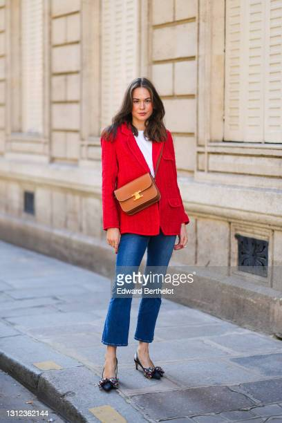 Therese Hellström @tesshell wears a red tweed jacket, a white t-shirt, a brown leather Celine bag, blue denim jeans pants, pointed bejeweled shoes,...