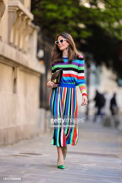Therese Hellström @tesshell wears white cat-eye sunglasses, a multi colored striped wool midi dress with long sleeves, a brown leather Hermes bag,...