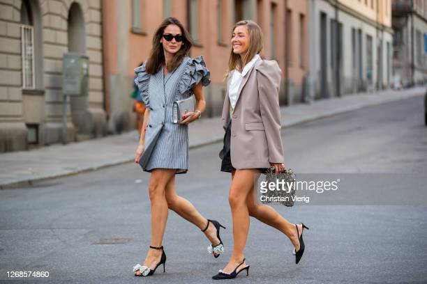 Therese Hellström wearing grey ruffled dress, clutch and My Andrén wearing brown blazer, black shorts, white blazer, clutch seen during Stockholm...
