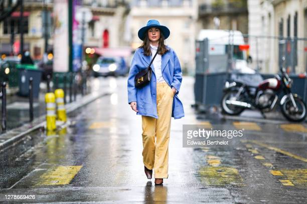 Therese Hellström wears a blue hat, a white ruffled shirt, a blue oversized blazer jacket, a Hermes bag, pale yellow corduroy pants, brown pointy...