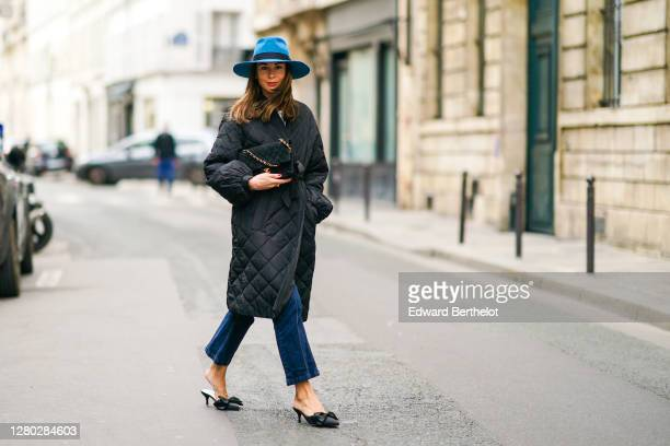 Therese Hellström wears a blue hat from Bronte, a black quilted Chanel bag with golden chain, a black padded puffer long coat from Custommade, blue...