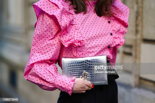 Therese Hellström wears a full Custommade look made of a neon pink ruffled oversized top with puff sleeves and printed polka dots, black pants, a...