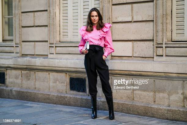 Therese Hellström wears a full Custommade look made of a neon pink ruffled oversized top with puff sleeves and printed polka dots, black pants, black...