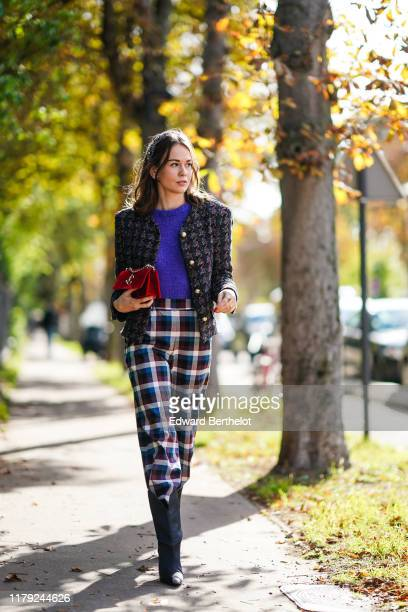 Therese Hellström wears a headband a colored tweed jacket a blue wool pullover a red bag checked pants outside Lacoste during Paris Fashion Week...