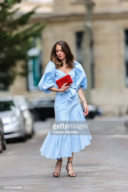 Therese Hellström wears a pale blue puffy sleeves V-neck belted long asymmetric dress, black suede strappy heels sandals with rhinestones details,...