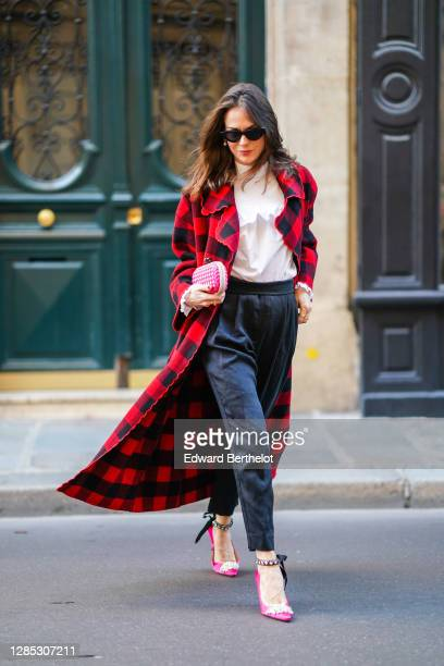 Therese Hellström wears a red and black checked coat from Manoush Paris, a white ruffled shirt blouse from Custommade, black pants from Custommade,...