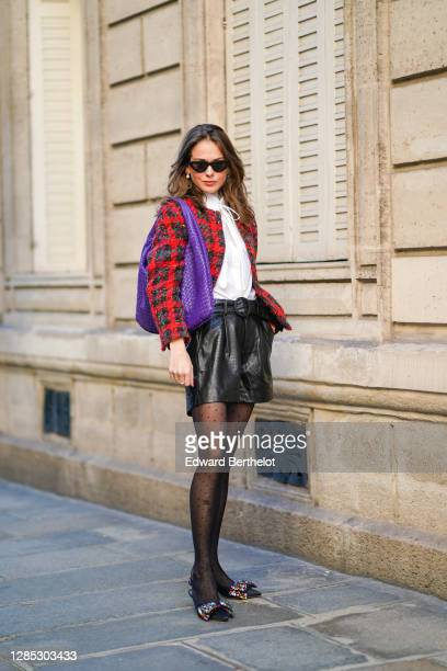 Therese Hellström wears a red checked knitted wool jacket, a white shirt blouse from Tory Burch, black leather shorts from Custommade, pointy colored...