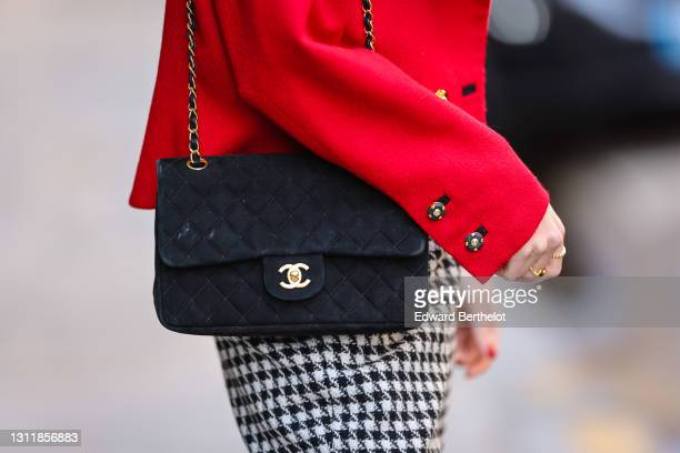 Therese Hellström wears a red jacket, a black Chanel bag, black and white pants with printed houndstooth patterns, on April 08, 2021 in Paris, France.