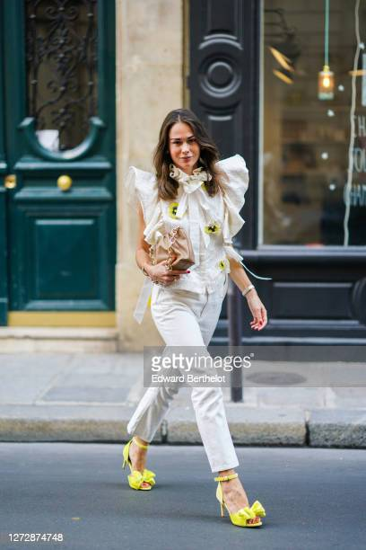 Therese Hellström wears a white ruffled top with embroidered yellow and black flowers and large shoulder parts from Custommade a brown leather bag...