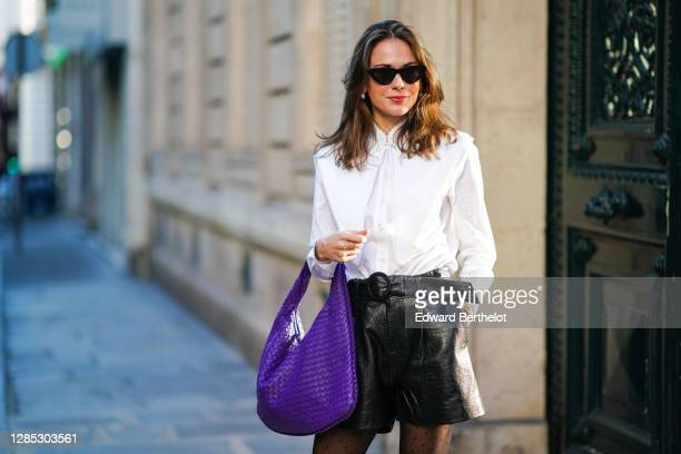 Therese Hellström wears a white shirt blouse from Tory Burch, black leather shorts from Custommade, a purple large woven leather bag from Bottega...