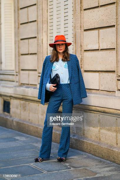 Therese Hellström wears an orange hat from Bronté Amsterdam, a navy blue blazer jacket with printed patterns and suit flared pants from Custommade, a...