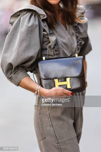 Therese Hellström wears black sunglasses, a gray denim puffy sleeves / V-neck / belted rolled-up / jumpsuit, a dark brown shiny leather Constance...