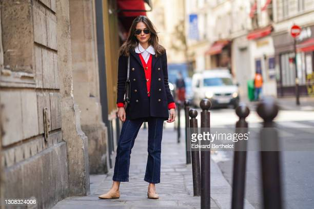 Therese Hellström wears Ray-Ban sunglasses, a white shirt with Peter Pan collar, a navy dark blue oversized military wool jacket with golden buttons,...