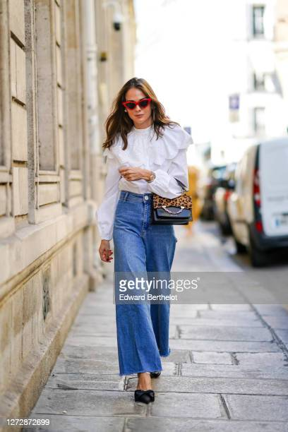Therese Hellström wears red Celine sunglasses, a white shirt / blouse from H&M with large ruffled collar, a black leather Karl Lagerfeld bag with a...