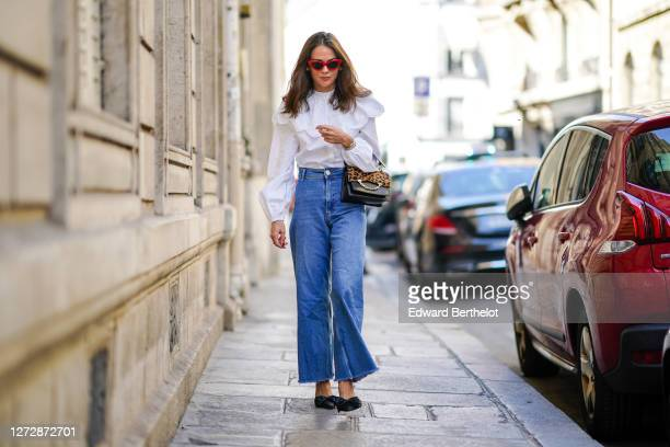 Therese Hellström wears red Celine sunglasses a white shirt / blouse from HM with large ruffled collar a black leather Karl Lagerfeld bag with a...