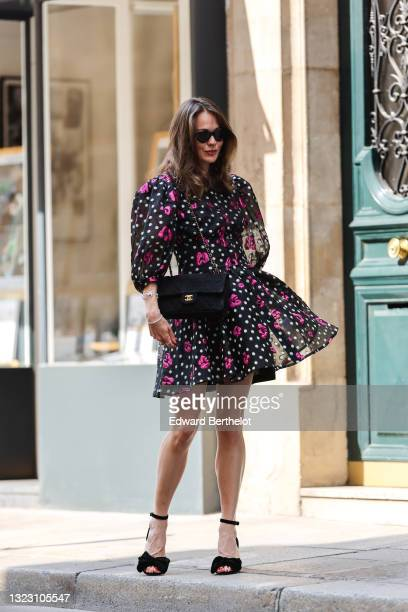 Therese Hellström wears sunglasses, a black transparent short dress with white spots and pink / fuchsia flower embroidered and puffy sleeves, a black...