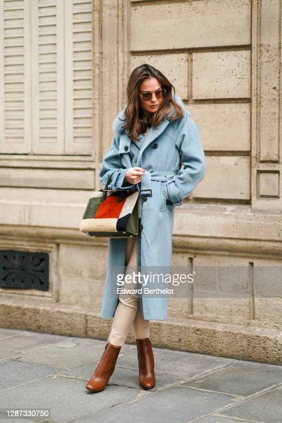 Therese Hellström wears sunglasses, a blue long winter wool trench coat with fluffy faux fur collar, white pants, a fluffy red and green khaki bag,...