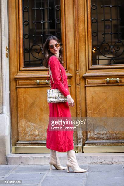 Therese Hellström wears sunglasses, a red midi long back-nude dress with sleeves, a Chanel bag, beige square toe high heels shiny boots, on April 08,...