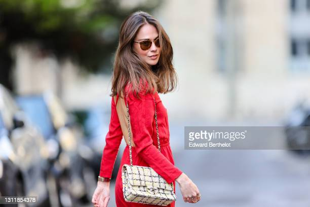 Therese Hellström wears sunglasses, a red midi long back-nude dress with sleeves, a Chanel bag, on April 08, 2021 in Paris, France.