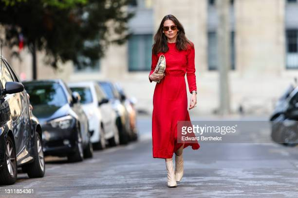 Therese Hellström wears sunglasses, a red midi long dress with sleeves, a Chanel bag, beige square toe high heels shiny boots, on April 08, 2021 in...