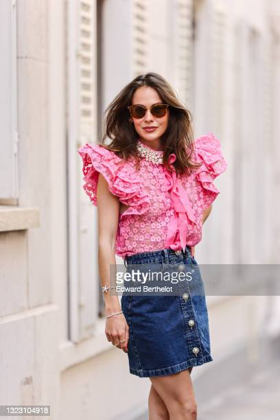 Therese Hellström wears sunglasses, a transparent pink puffy sleeves shirt with flowers embroideries and knotted scarf, and white pearls on the...