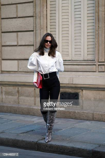 Therese Hellström wears sunglasses, a white shirt with puff shoulders / sleeves, a red leather bag, black pants, knee-high pointy boots with gray...