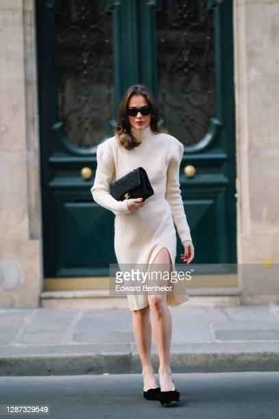 Therese Hellström wears sunglasses, a white wool turtleneck slit dress with shoulder pads, a Chanel bag, black pointy shoes, on November 19, 2020 in...