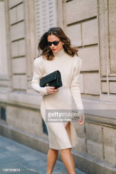 Therese Hellström wears sunglasses, a white wool turtleneck slit dress with shoulder pads, a Chanel bag, on November 19, 2020 in Paris, France.