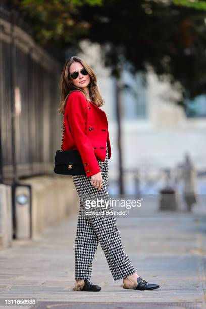 Therese Hellström wears sunglasses, earrings, a red military jacket with shoulder pads and golden buttons, a white t-shirt, a black Chanel bag, black...