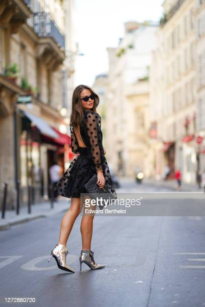 Therese Hellström wears sunglasses from Chimi Eyewear, an open back black mesh pleated / ruffled black dress with printed polka dots from By Malina,...