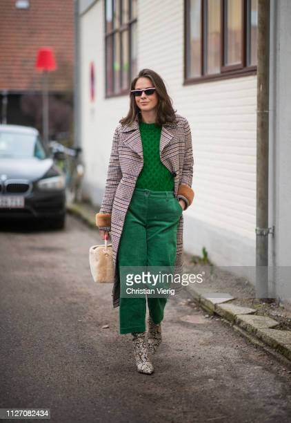 Therese Hellstroem is seen wearing boots with snake print, teddy bag, plaid coat, green pants outside Baum und Pferdgarten during the Copenhagen...