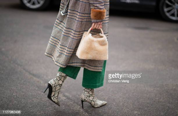 Therese Hellstroem is seen wearing boots with snake print teddy bag plaid coat green pants outside Baum und Pferdgarten during the Copenhagen Fashion...