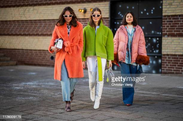 Therese Hellstroem is seen wearing wide leg denim jeans, red teddy coat, plaid multi colored bag and Nina Sandbech is seen wearing green jacket, hair...
