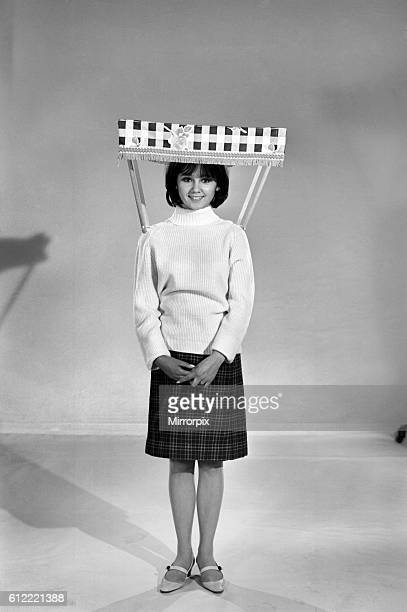 Therese Howard Jones demonstrating the wear-me umbrella. Model . Circa 1959
