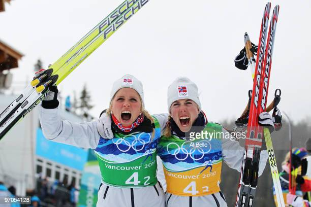 Therese Johaug of Norway and Kristin Stoermer Steira celebrate winning the gold medal during the Ladies' Cross Country 4x5 km Relay on day 14 of the...