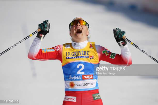 Therese Johaug of Norway celebrates as she crosses the finish line to win the Cross Country Skiathlon Ladies 15k race during FIS Nordic World Ski...