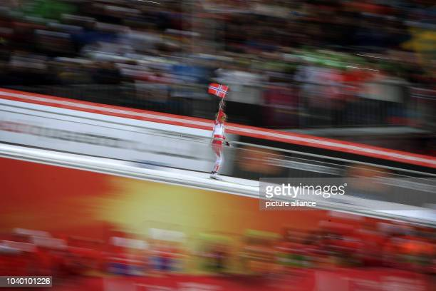Therese Johaug of Norway celebrates towards the finish and waves a national flag of Norway during the cross country Ladies 30 Kilometers Mass Start...