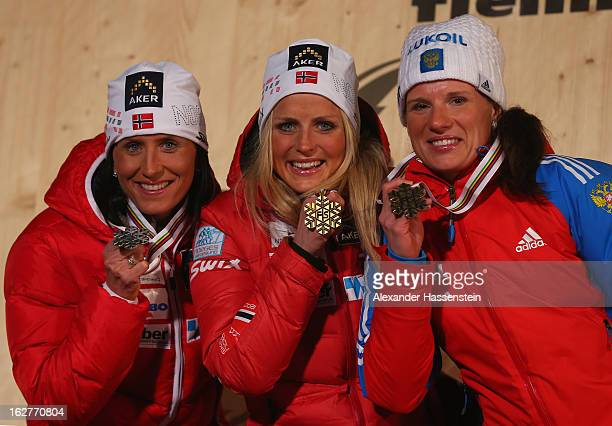 Therese Johaug of Norway celebrates with her Gold medal, Marit Bjoergen of Norway her Silver medal and Yulia Chekaleva of Russia her Bronze medal, at...