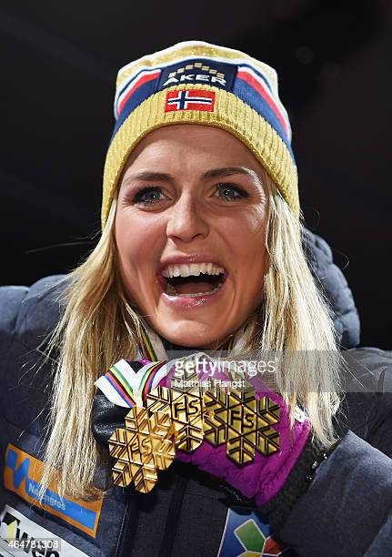 Therese Johaug of Norway poses with her three gold medals during the medal ceremony for the Women's 30km Mass Start CrossCountry during the FIS...