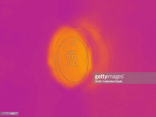 Thermal camera thermographic image, with light areas corresponding to higher temperatures, waste heat generated by Nest Learning Thermostat in a...